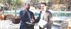 Dr Leonardo S. Simão and Mr Werner Myburgh shake hands on the project implementation contract