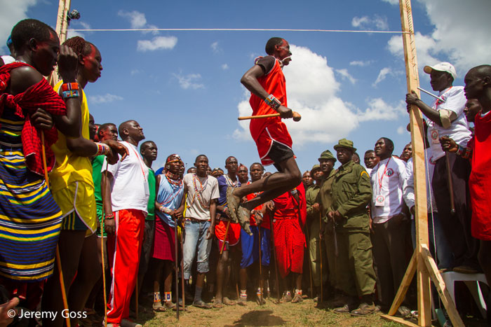 A warrior flies through the air in the standing high jump; the goal is to touch the rope with your head.