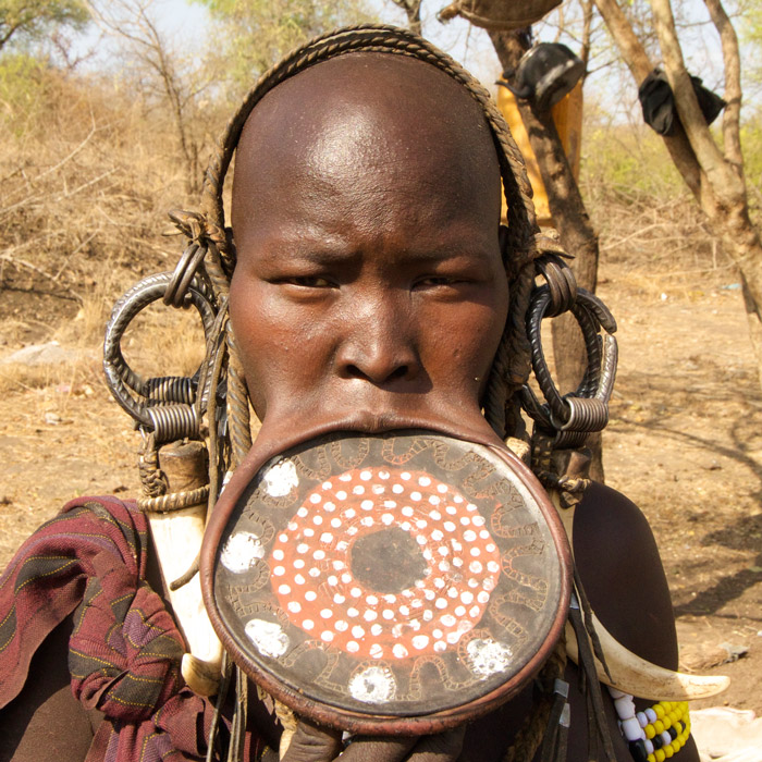 Women wear clay plate through lower lip and earlobes