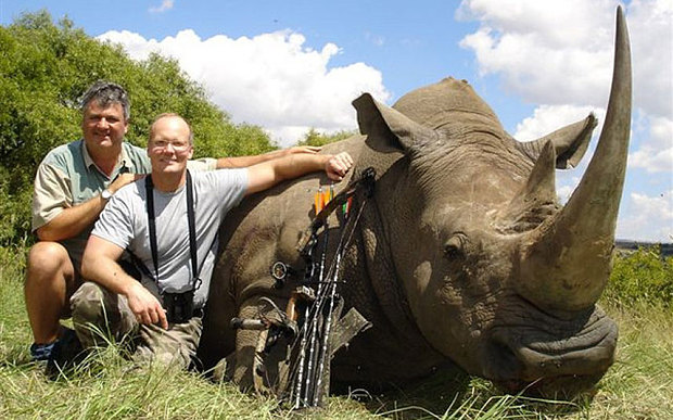 "Walt Palmer, middle, with the ""world record"" white rhino killed by bow in South Africa. Mr Palmer is pictured with Pierre Vorster, a professional hunter"