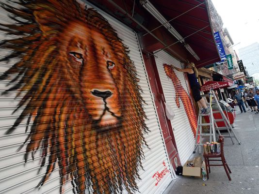 Artist J. Morello, after completing a painting of Cecil the Lion, works on another painting on a store front in New York. © Don Emmert, AFP/Getty Images