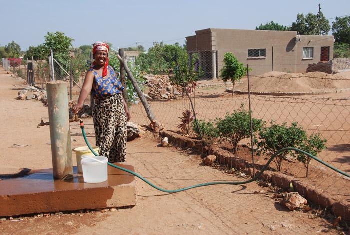 Paulina Malatji filling up a bucket from a communal tap next to her home in Lerupurupung ©Heather Dugmore