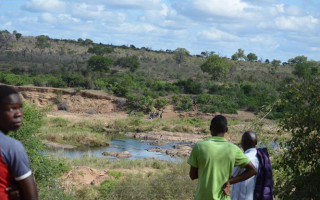 Spectators in Marloth Park watched as the lifeless body of a poacher killed in action, as well as other suspects being taken away from the banks of the Crocodile River after an early morning shootout with rangers.