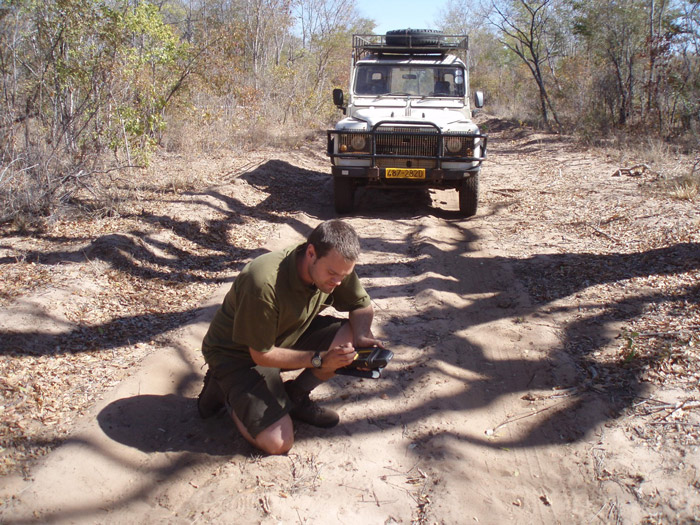 The author recording carnivore spoor in Zimbabwe. ©Sam Williams