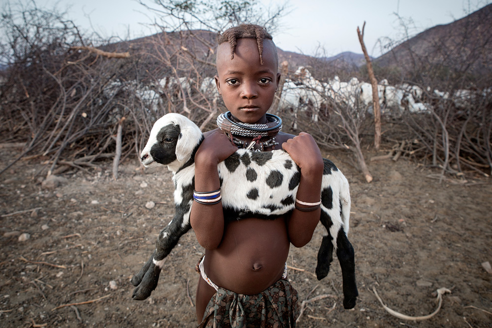 A child with its goat in Otjimazeva Village in the Epupa region of Namibia ©Ben Mcrae