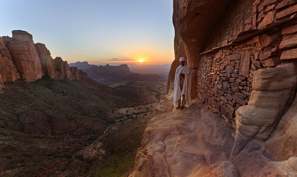 The sun sets in Tigray behind an Ethiopian orthodox priest ©Greg Metro