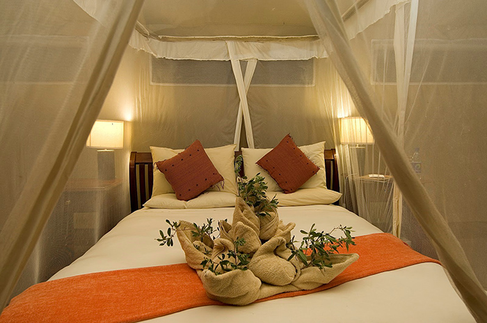 Crawl into bed and get cozy at Linyanti Bush Camp in Botswana