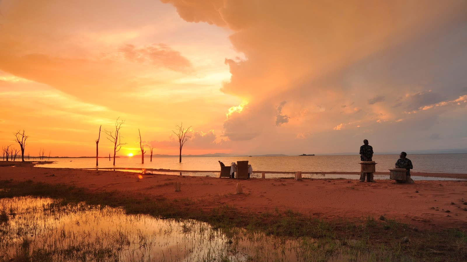 Guides bask in the views of the sun setting on the water of Lake Kariba in Bumi Hills, Zimbabwe