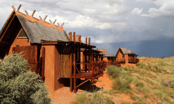 The guest chalets at !Xaus Lodge atop red dunes covered by desert grasses