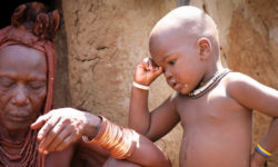 Young Himba child contemplates his grandmother busy with chores in Kunene, Namibia