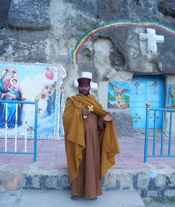 Ethiopian priest standing outside his church