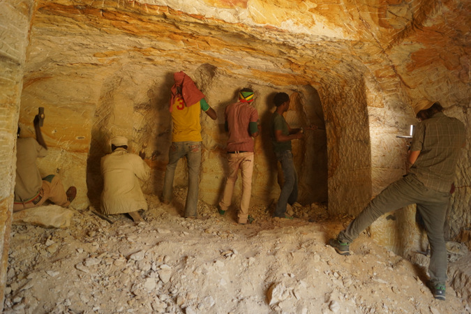 Team of chisellers working on a large piece of rock in Ethiopia