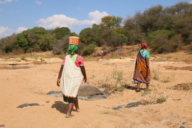 Woman make their way back to camp after collecting sand from the riverbed
