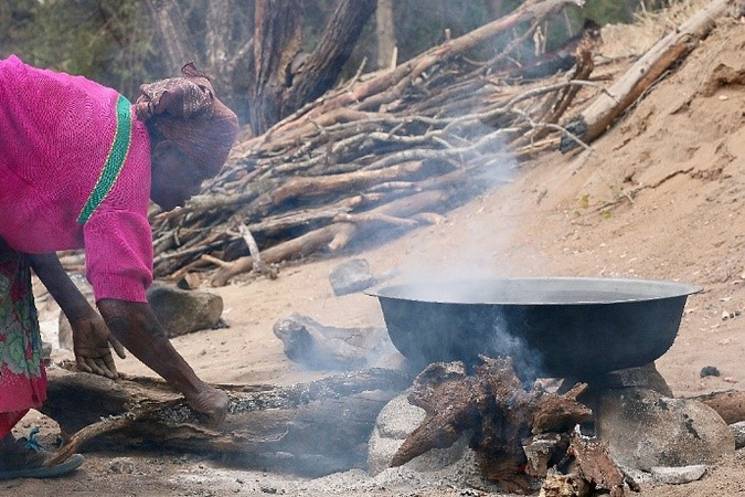 Salt boils away in a black pan over the fire while a woman tends to it