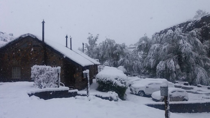 Heavy snowfall in Lesotho, car and houses covered in snow