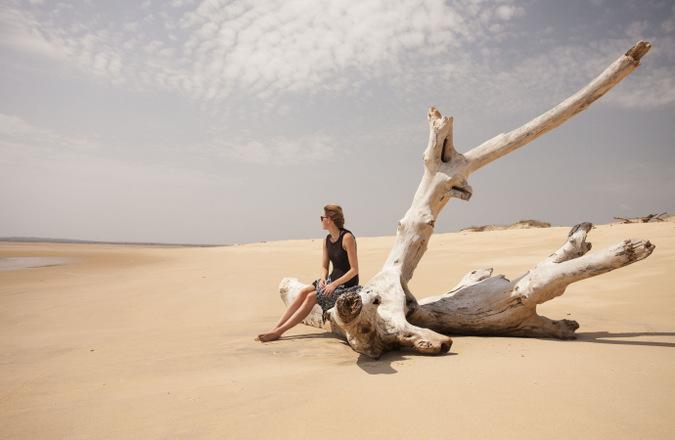 Person sitting on drift wood on empty beach in Lamu, Kenya