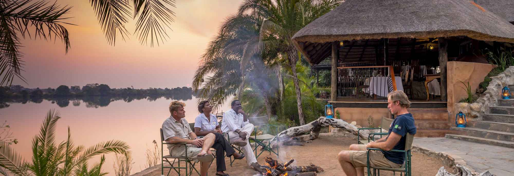 People relaxing by a pit fire by the Kafue River in Zambia