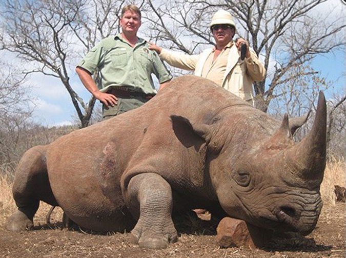 Two hunters posing with killed rhino
