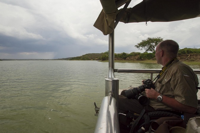 Photographer on cruise boat on Kazinga channel in Queen Elizabeth NP in Uganda