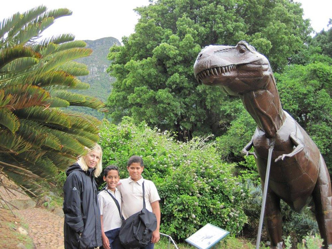 Students with cycads and sculpture of dinosaur in Kirstenbosch Botanical Gardens, South Africa