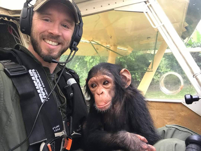 Pilot with rescued baby chimpanzee in DR Congo