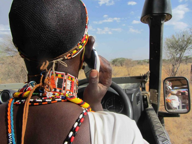 Maasai warrior with cellphone driving a game drive vehicle