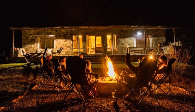Guests sitting around a fire at Karoo Lodge Conservancy, Karoo, South Africa