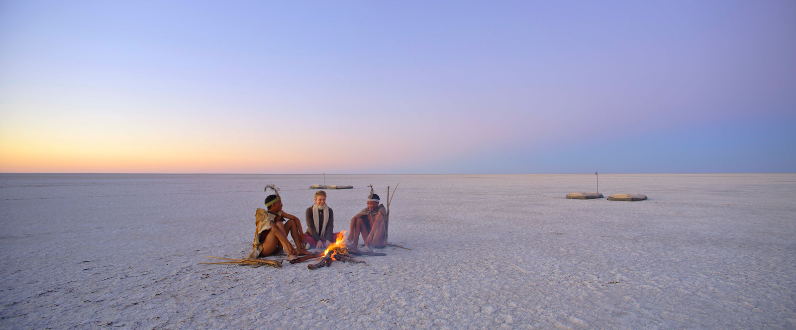 Khoisan and guest sitting in salt pan in Botswana