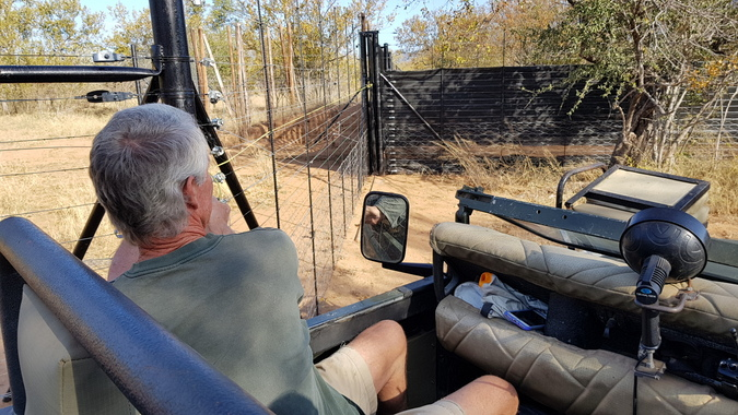 Person in safari vehicle about to open boma door