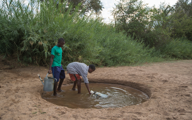 Children collecting water from dry riverbed in Mfuwe in Zambia
