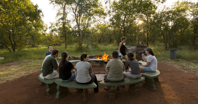 Bushwise field guide students around a fire pit