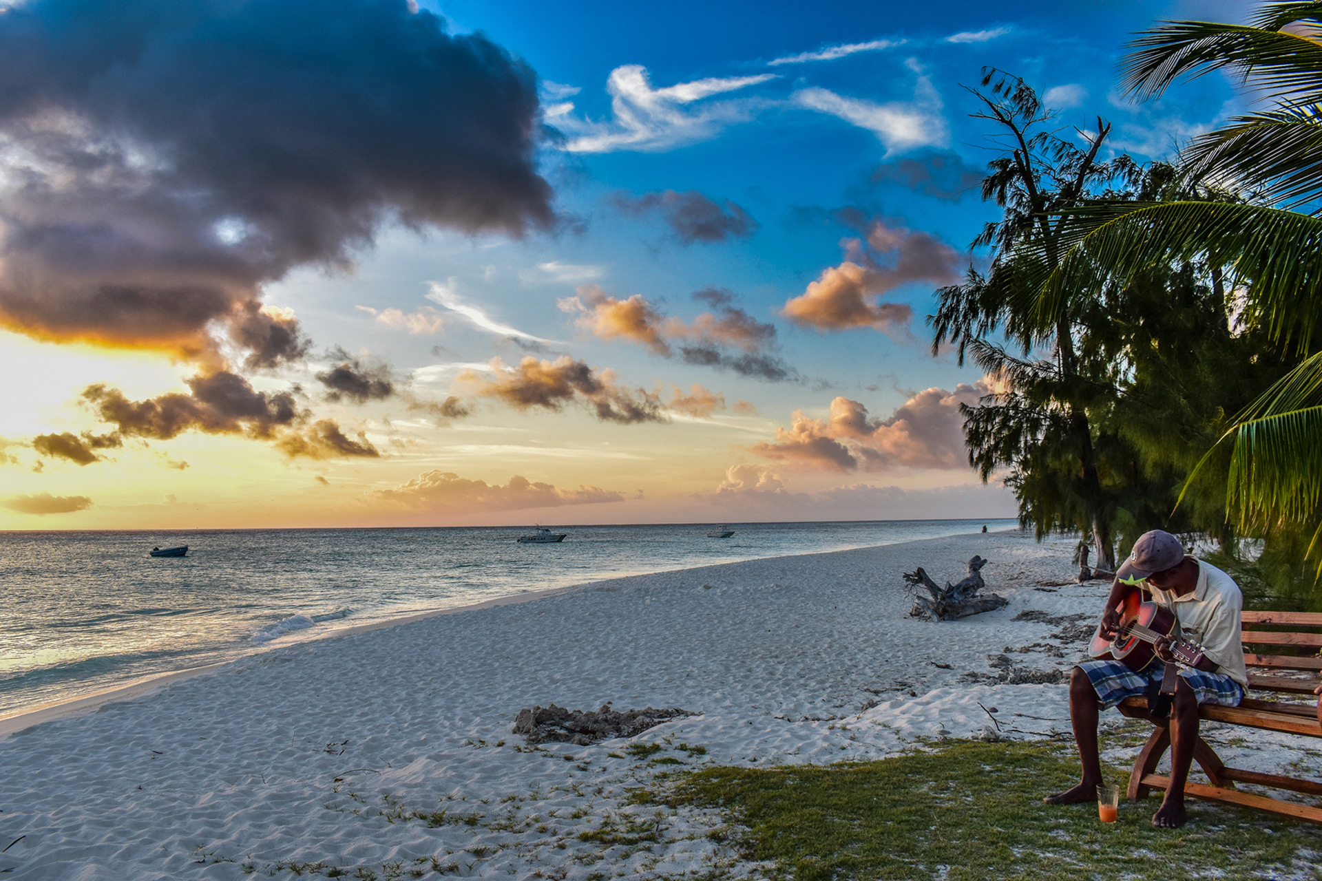 Man playing guitar on one of Aldabra's beaches in Seychelles