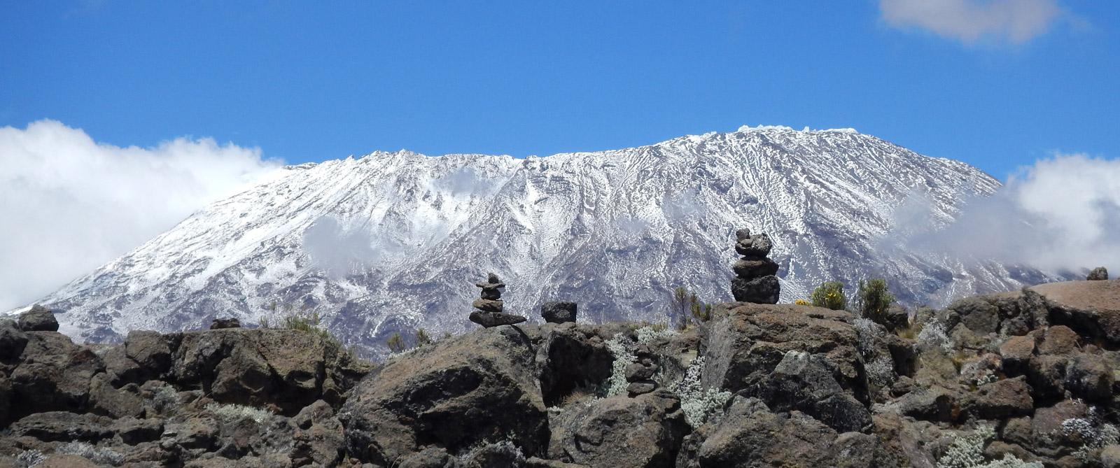 Rock cairns dwarfed by Mount Kilimanjaro in the distance © Shelley Hyne