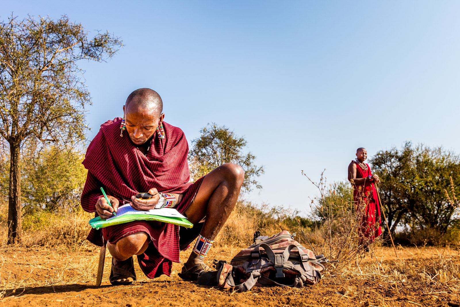 Maasai Kamunu Saitoti takes meticulous notes about his observations while tracking lions in Amboseli