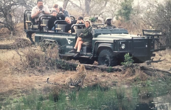 Leopard with safari vehicle and guests