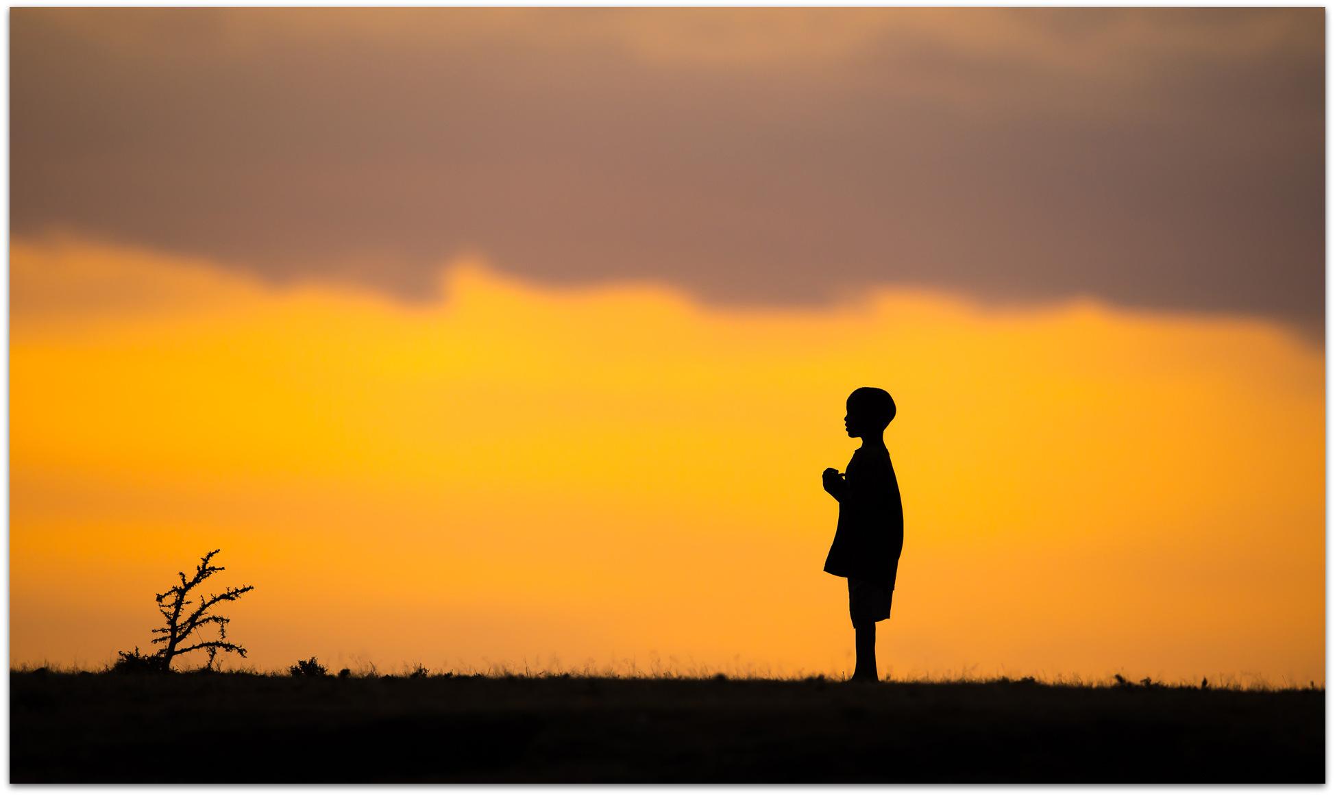 Maasai child against sunset in Maasai Mara
