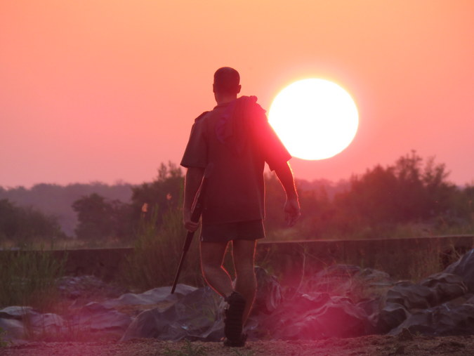 Ranger walking into the sunset in Kruger National Park in South Africa