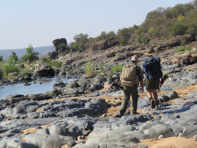 Two rangers walking by river in Kruger National Park in South Africa
