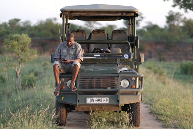 Field guide sitting on game drive vehicle