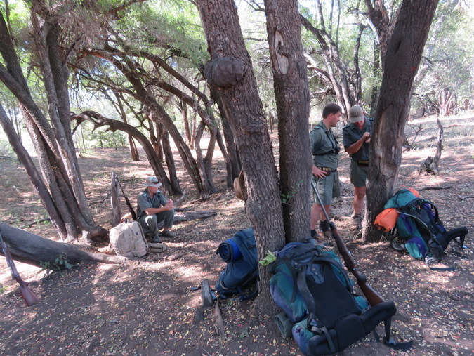 Rangers resting with backpacks in a forest in Kruger National Park in South Africa