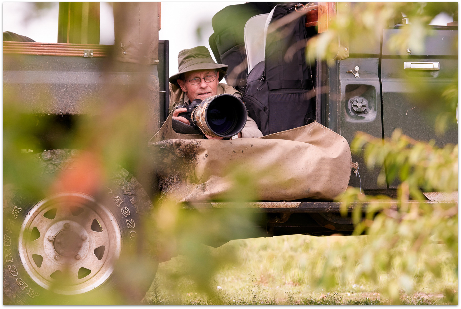 Photographer taking photos from a specially-adapted photographic safari vehicle