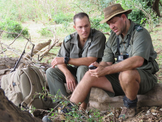 Two rangers sitting down looking at a GPS in Kruger National Park in South Africa