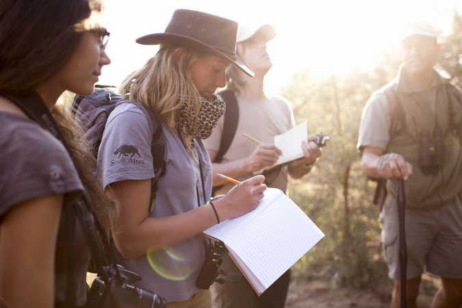 Safari guide students in the wild taking notes