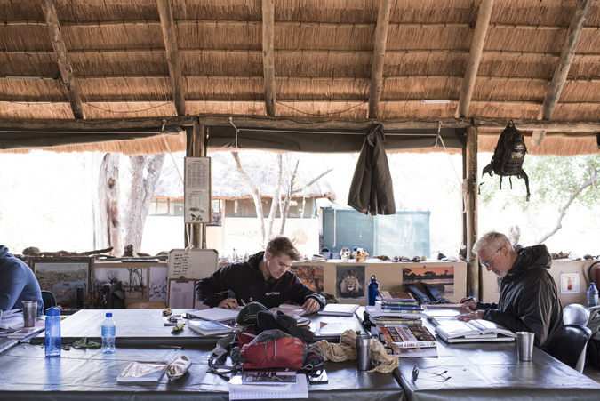 Two EcoTraining students studying in the open boma in the bush