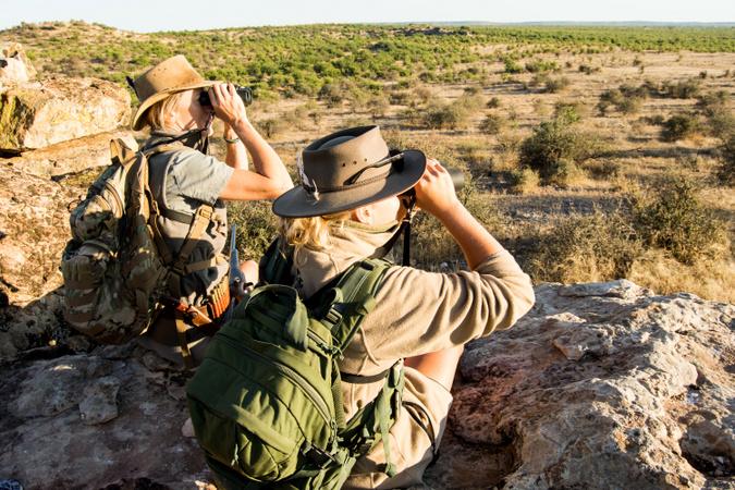 Two safari guide students using binoculars