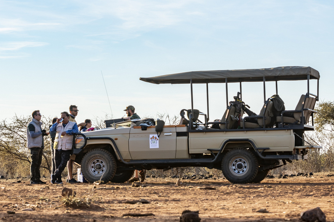 Guests having a drinks break by a game viewing vehicle while on safari in Madikwe Game Reserve