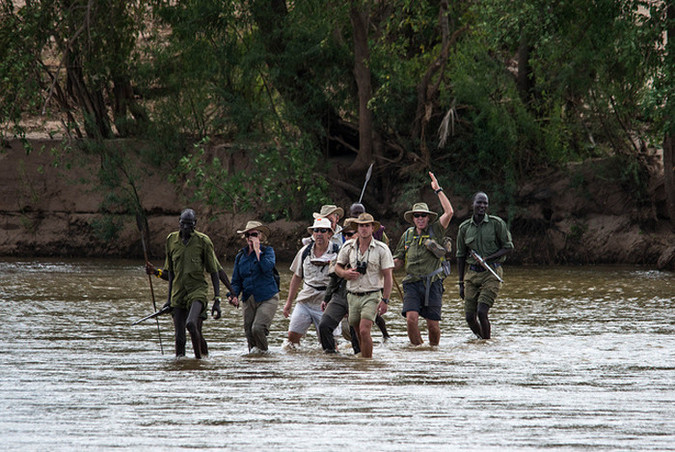 A walking safari group crossing Athi-Galana-Sabaki River in Kenya