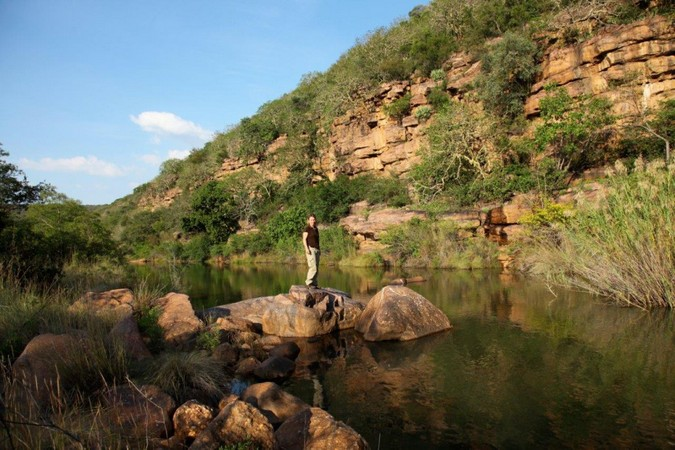Person standing on a rock by a river in the Waterberg in South Africa