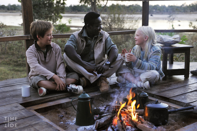 Zambian guide with children around the camp fire