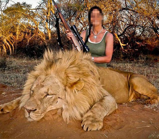 Hunter with dead lion, trophy hunting